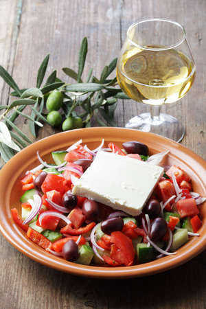 Greek salad with goats cheese and white wine photo
