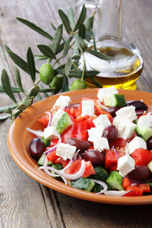 Greek salad on the rustic plate and olive branch photo