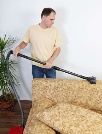 Man vacuums a sofa photo