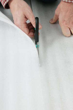 underlay: La mano del hombre con unas tijeras cortando la capa base para la instalaci�n de suelos laminados