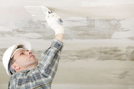 Contractor in white hardhat plastering a ceiling photo