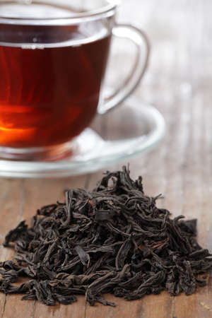 pekoe: Heap of dried tea leaves and a cup of black tea Stock Photo