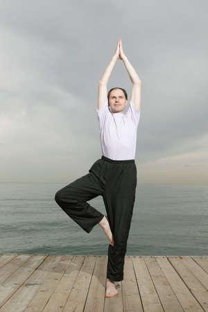 Man doing yoga on beach photo