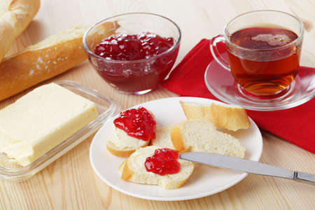 Breakfast with baguette, butter, jam, and tea