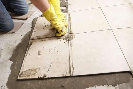 Tiler installing ceramic tiles on a floor photo