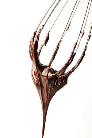 egg whisk: Whisk with liquid chocolate Stock Photo