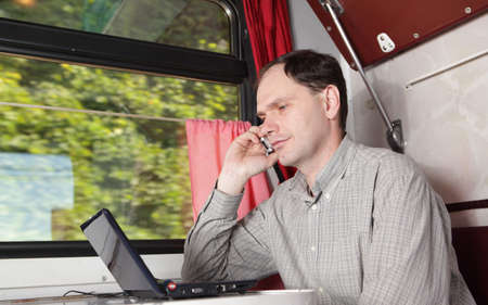 netbook: Man in train with laptop and cellular phone