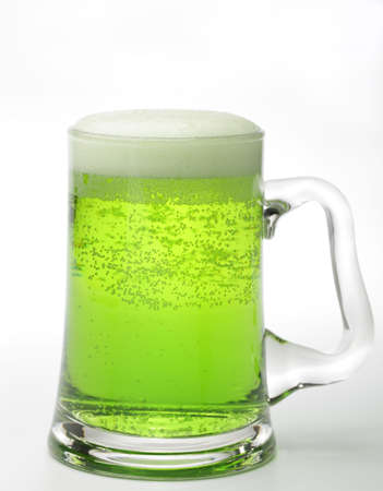Glass of green beer isolated on white photo