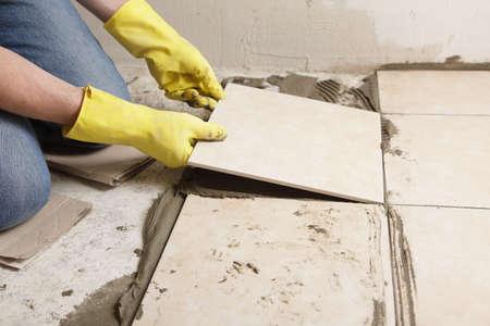 azulejos ceramicos: Tiler instalaci�n de baldosas de cer�mica en un piso Foto de archivo