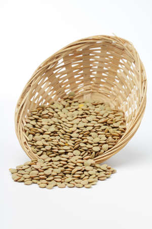 Brown lentils scattered from a small basket isolated on white photo