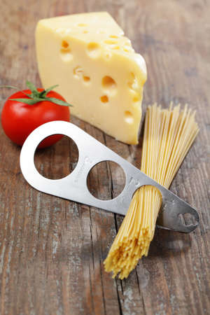 Spaghetti portioner, piece of yellow cheese, and tomato photo