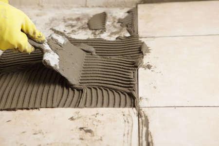 pegamento: La instalaci�n de baldosas de cer�mica en un piso de Gu�rin  Foto de archivo