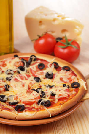 Pizza with cheese, tomato, and olives
