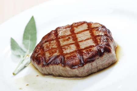 Beef steak on white plate closeup