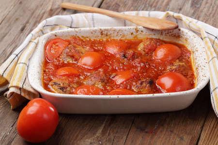 Meatballs with tomato prepared in white casserole photo