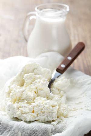 cagliata: Ricotta in una garza contro una brocca di latte