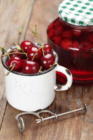 mermelada: Taza con frescos cereza de agria y una jarra con mermelada
