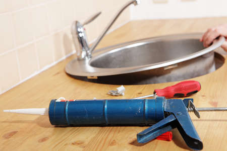 Caulking gun with silicone sealant against kitchen sink installation process photo