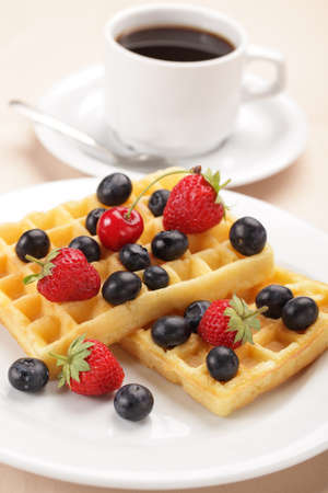 Breakfast with coffee and belgian waffles with strawberry, cherry and blueberry photo