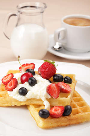 Belgian waffles with whipped cream, strawberry, cherry and blueberry photo