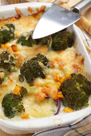 Gratin with broccoli, carrot, onion and cheese in white casserole photo