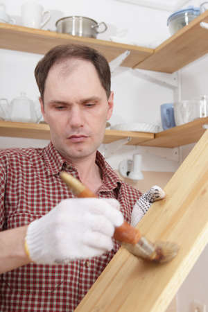 kitchen renovation: Man varnishing wood shelves for kitchen renovation
