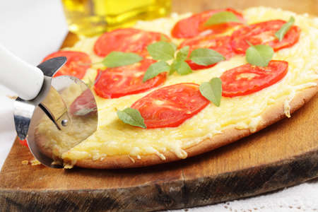 Cutting Margharita Pizza on a wooden cutting board photo