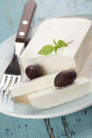 queso de cabra: Bloque de queso feta con hojas de albahaca y aceitunas de calamata  Foto de archivo