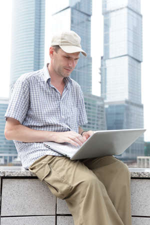 office buildings: Man with laptop against modern office buildings Stock Photo