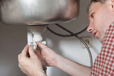 Man installing a drain for a kitchen sink photo
