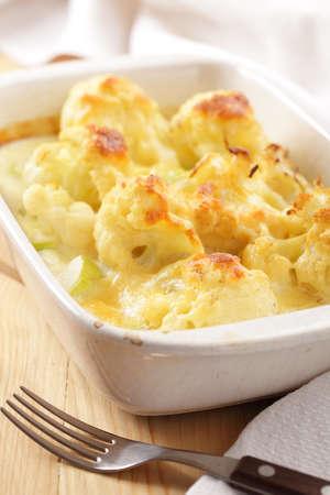 Vegetable gratin in white casserole closeup photo