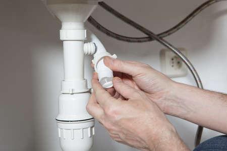 desague: Hombre instalar un drenaje de un receptor de cocina