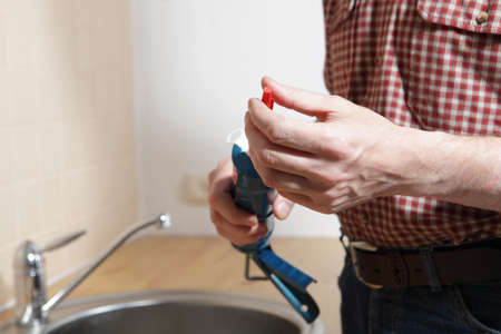 sealant: Plumber with silicone sealant in a caulking gun Stock Photo