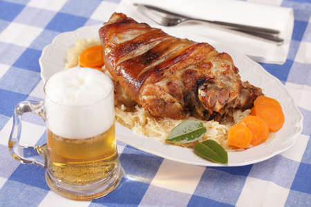 Eisbein, roasted pork knuckle with braised cabbage and beer photo