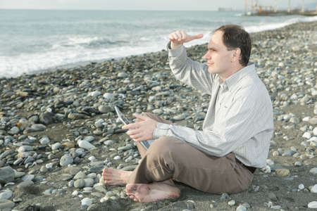 Barefooted man working with laptop on the beach photo