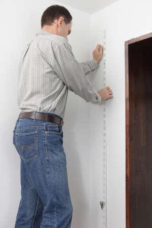 determining: Hombre determinar las direcciones verticales mediante whileout de bob plumb montaje del armario Foto de archivo