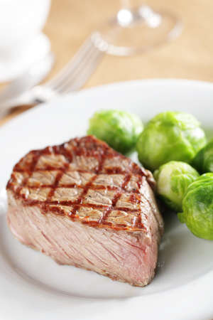 Grilled steak with steamed Brussels sprout on white plate closeup
