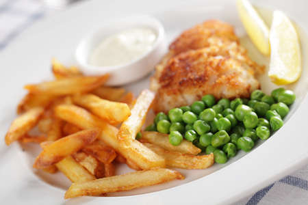 French fries, roasted fish, green peas, lemon, and sauce photo