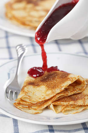 hotcakes: Crepes with cranberry jam on white plate closeup