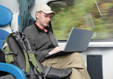 Tourist with backpack and laptop in the train photo