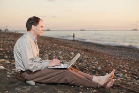 Man with laptop on the beach watching sunset photo