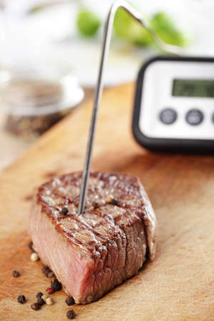 Grilled steak on the cutting board with temperature controller inside photo