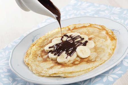 Crepes with banana and chocolate sauce photo