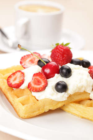 Belgian waffles with whipped cream, strawberry, cherry and blueberry