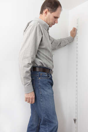 determining: Man determining the vertical directions using plumb bob whileout assembling the closet