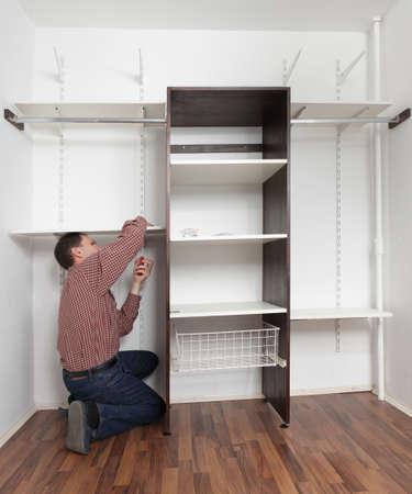 Man assembling the closet with wooden shelves