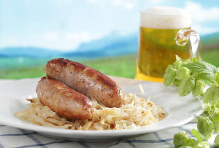 Roasted sausage with braised cabbage and beer against mountain background