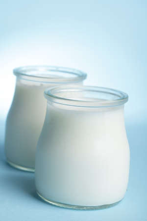 Two jars with yogurt against blue background Stock Photo