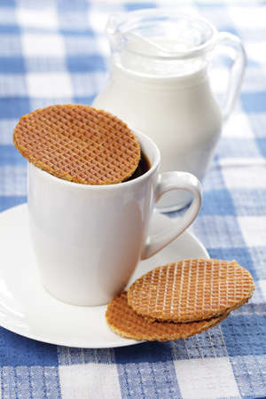 treacle: Stroopwafel on the cup of coffee and the jug with milk