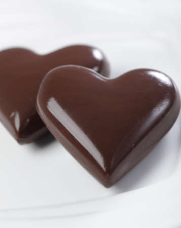 dark chocolate: Two chocolate hearts on white plate closeup